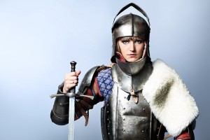 Portrait of a medieval female knight in armour over grey backgro