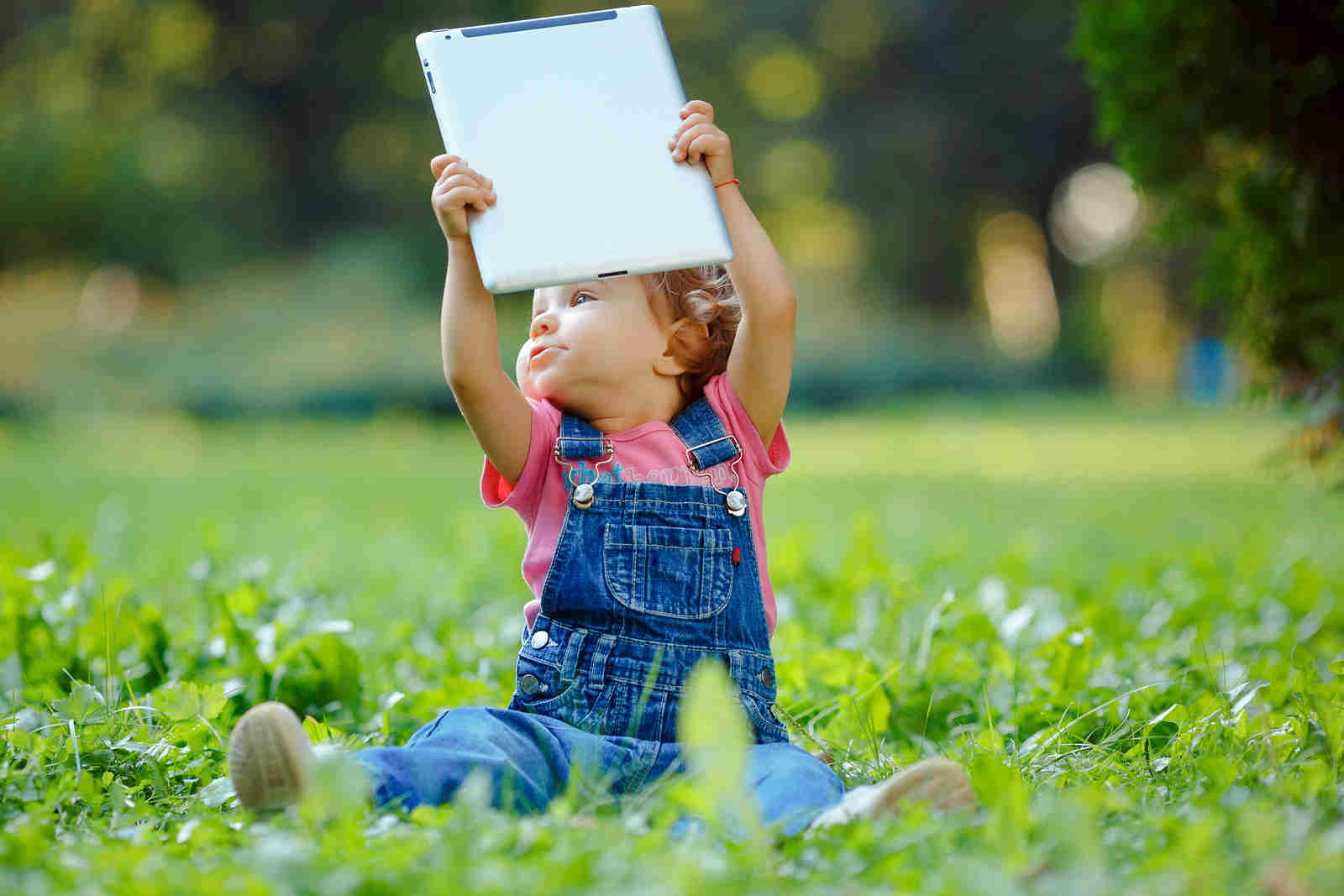 Child playing with tablet outdoors. Cheerful child with a portable PC in your hands. Child holding a tablet over his head.